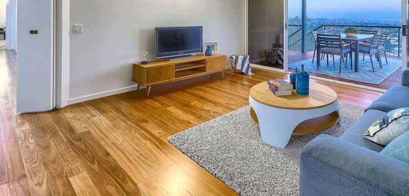 Living room floor polished with a rug and chair on it..