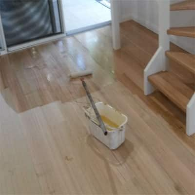 Polishing a raw timber floor with a roller.