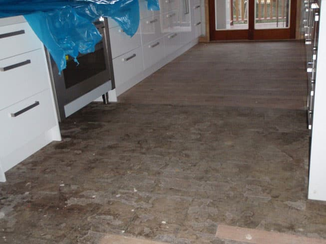 A kitchen floor with glue on it before a sand.