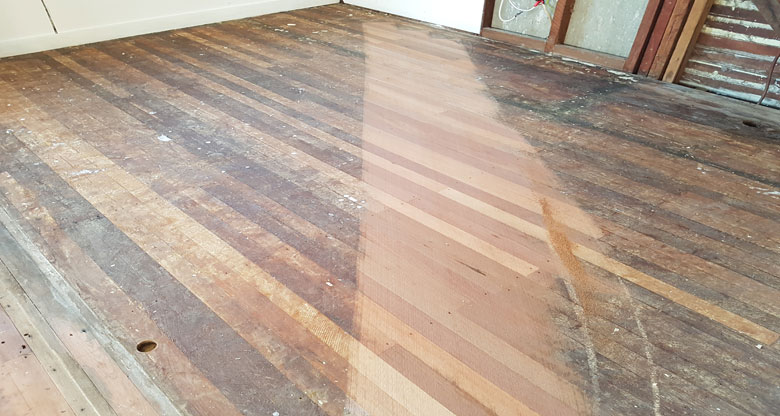 An old floor showing a sanded section of hardwood flooring.