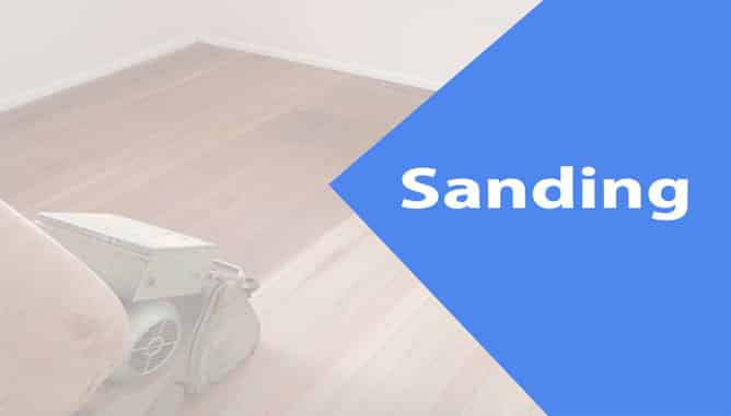 Electric sander machine with fine abrasive grit sandpaper sanding dressed timber floorboards.