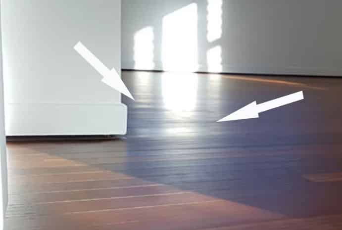Arrows pointing to depressions in timber floor surface.
